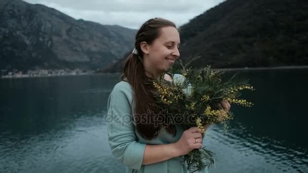 Young woman holds bouquet of mimosa, inhales fragrance near lake.