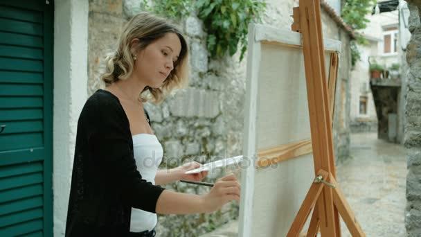 Donna artista disegna la pittura dalla vita su cavalletto allaperto
