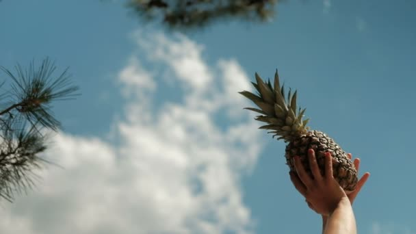 Shooting from bottom of girl hand raises pineapple up, rests on beach