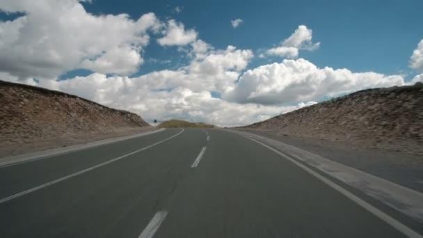 Vozidlo jede po zemi silnici v oblačné počasí.