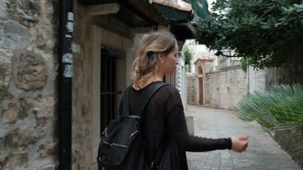 Mladá blond žena chodí na ulici s kamennými budovami