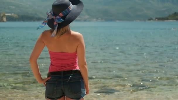 Mladá žena stojí na pláži v slunné odpoledne