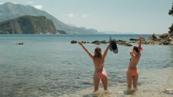 Zwei Frauen stehen an einem Sommertag am Ufer des Meeres. attraktive Menschen in rosa Badeanzügen