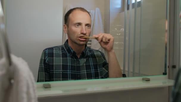 A fiatalember fogmosás a fürdőszobában bent állva.