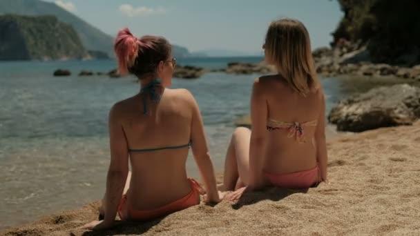 Dvě mladé ženy synchronně spadají na zádech na pláži