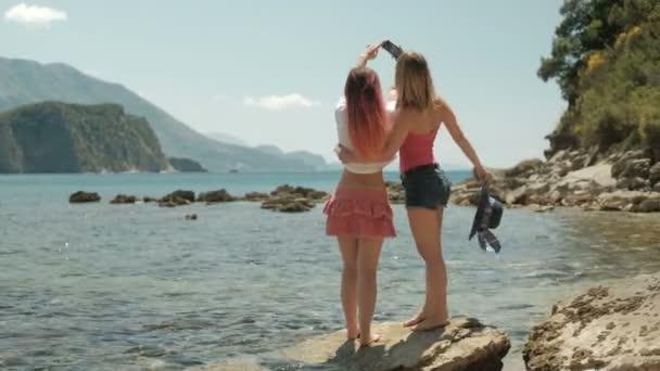 Dvě ženy dělají selfie na telefonu na skále na pláži
