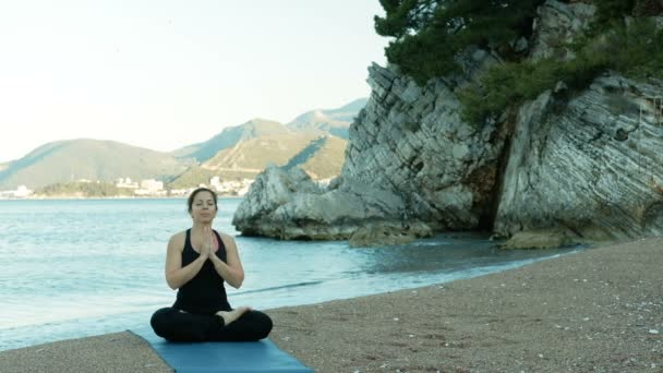 An adult woman meditates with her eyes closed in a lotus pose on beach