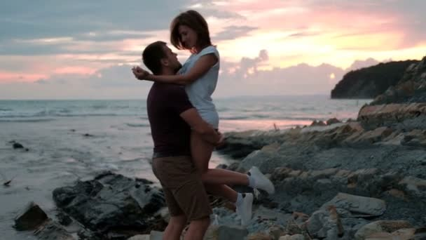 Young man holding woman, standing on beach on summer evening outdoors.