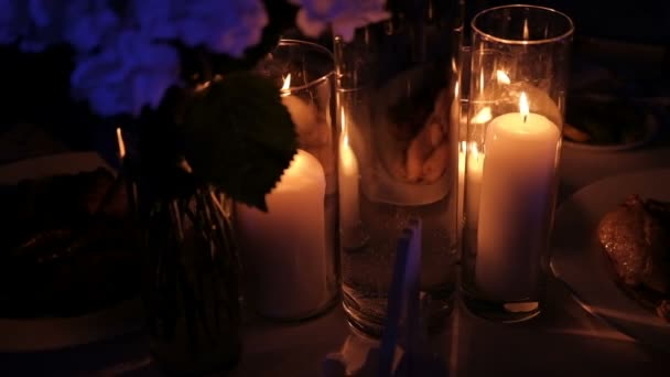 Burning candles inside glass flasks stand on table in room.