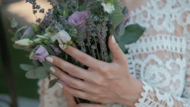 Mladá nevěsta drží kytici květin v rukou stojící uvnitř