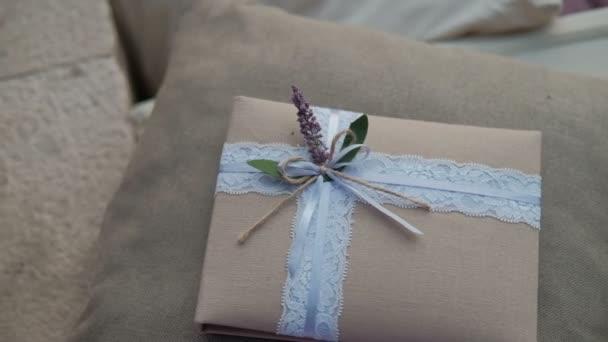 Dárek v balíčku tkáně s jemné stuha a květ leží na polštáři v pokoji