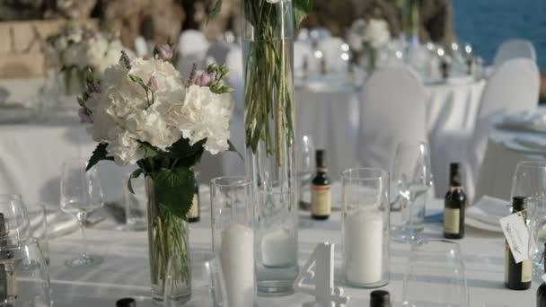 Bílé květy ve váze jsou nastaveny na tabulkách na oslavu po moři