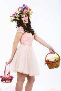 Smiling woman holding Easter basket with colored eggs