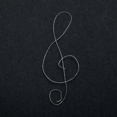 Musical sign clef on black paper