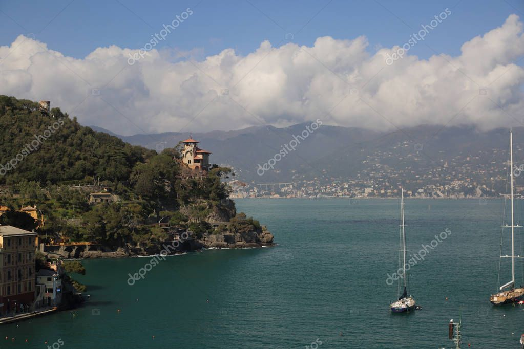 PORTOFINO, ITALY - APRIL 5, 2018: Luxury Italian vacations - beautiful Portofino in Ligurian coast. View of the bay with blue water and yachts in Portofino, through the village crown.