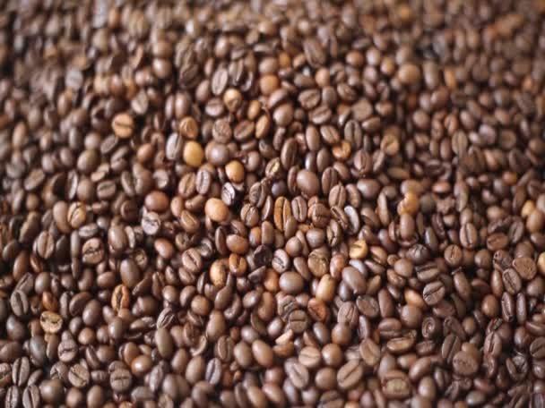 Video klip z hnědých pražených kávových zrn je mix arabica a robusta. Sada krátkých záběrů spojených jednoduchou montáží.