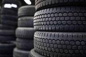 Pneumatiky prodej v obchodě pneumatiky - hromádky starých použité pneumatiky