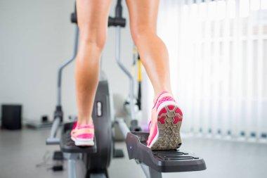 Young woman's muscular legs on stepper/treadmill, closeup