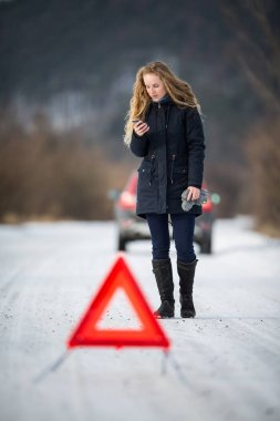 Young woman setting up a warning triangle and calling for assistance