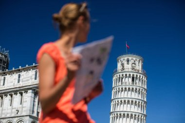 Gorgeous female tourist with map admiring the Leaning Tower of Pisa