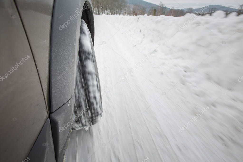 Car with winter tires on a slippery, snowy road - motion blur