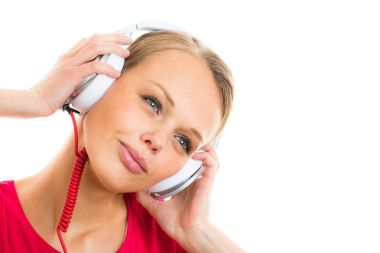 Pretty, young woman listening to her favorite music on hi-fi  headphones