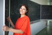 Csinos, fiatal főiskolás diák ír a táblára / blackboára