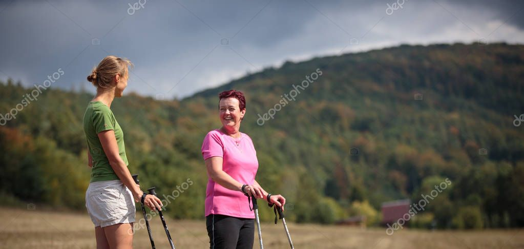 Pretty, young woman nordic walking on a forest path, taking in t