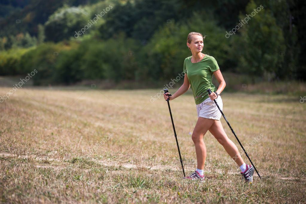 Pretty, young woman nordic walking on a forest path