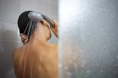 Pretty, young woman taking a long hot shower washing her hair