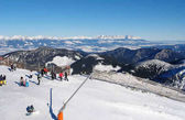 Lyžaři za slunečného dne na horu Chopok v letovisku Jasna