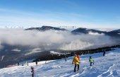 Lyžaři na sjezdovce za slunného dne v letovisku Jasná