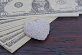 Dollar banknotes and heart on a wooden table
