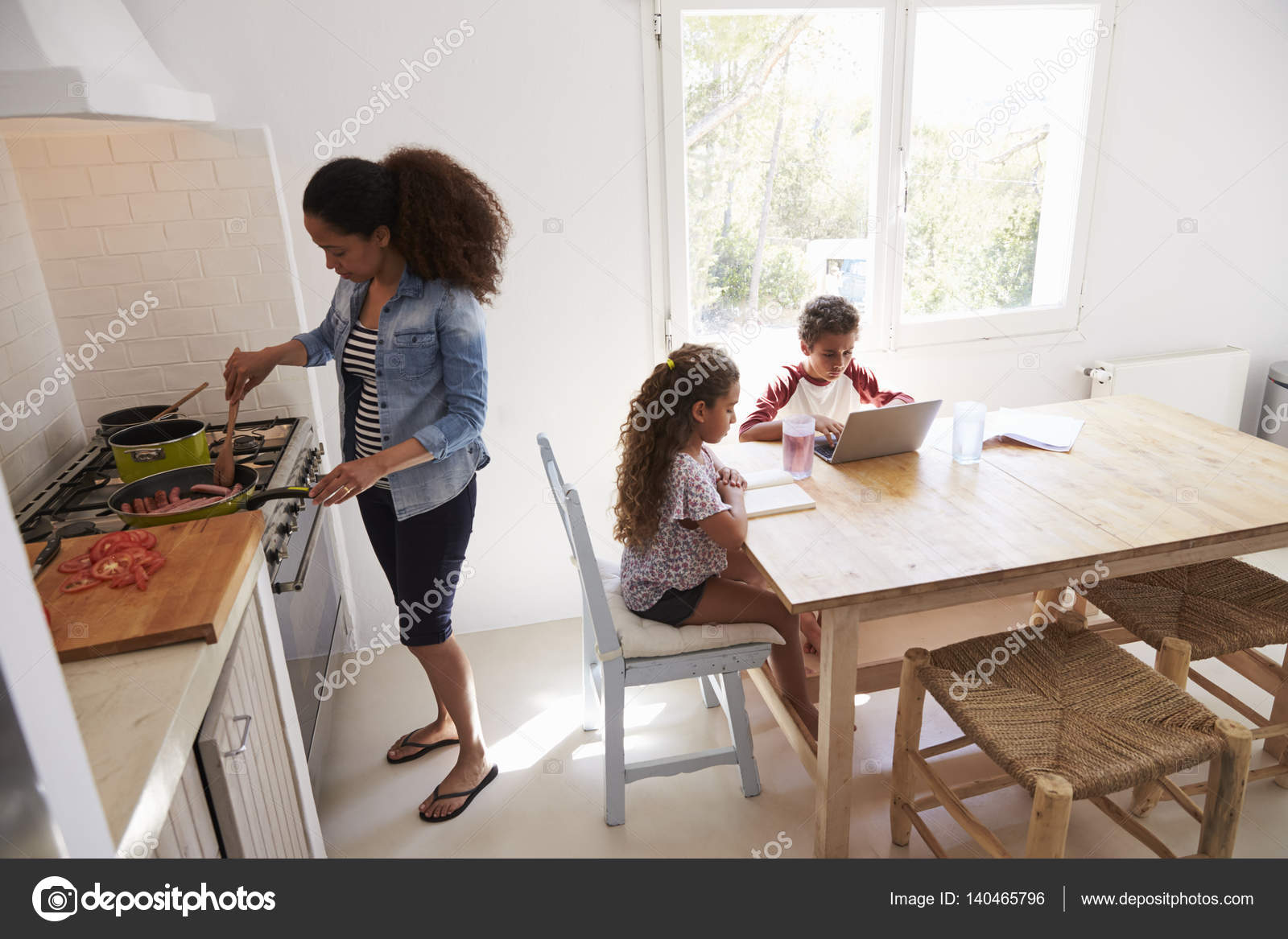 Mum cooking and kids working in kitchen stock photo mum cooking and kids working on computers kitchen table photo by monkeybusiness workwithnaturefo