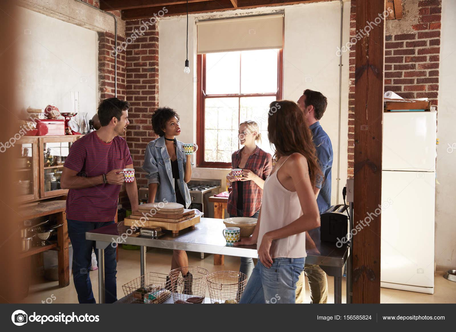 Vrienden praten over koffie in keuken u stockfoto monkeybusiness