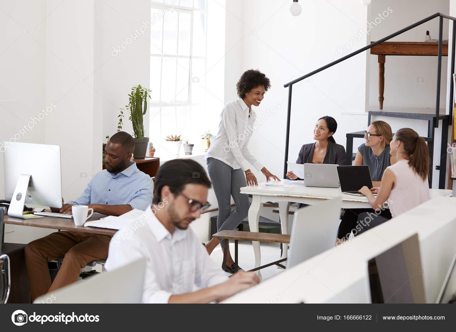 Vrouw briefing collega s rond bureau u stockfoto monkeybusiness