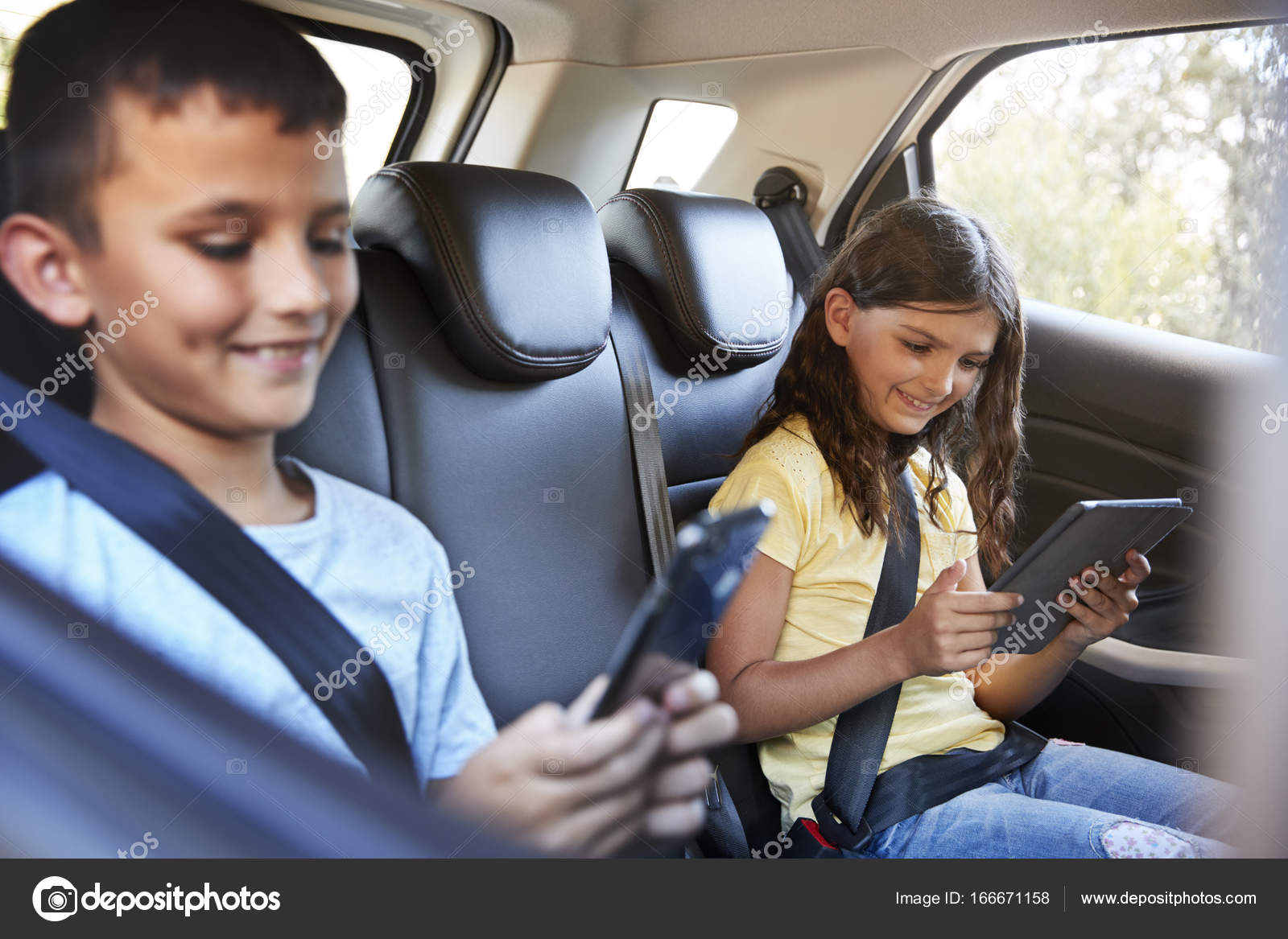 boy and girl in car using tablets stock photo monkeybusiness