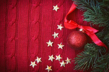 Christmas red knitted background with branch fir