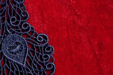 Detail of black lace on red velvet