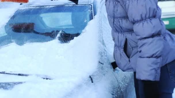 Frau reinigt Auto vom Schnee