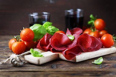 Dish of italian traditional bresaola with red wine, selective focus