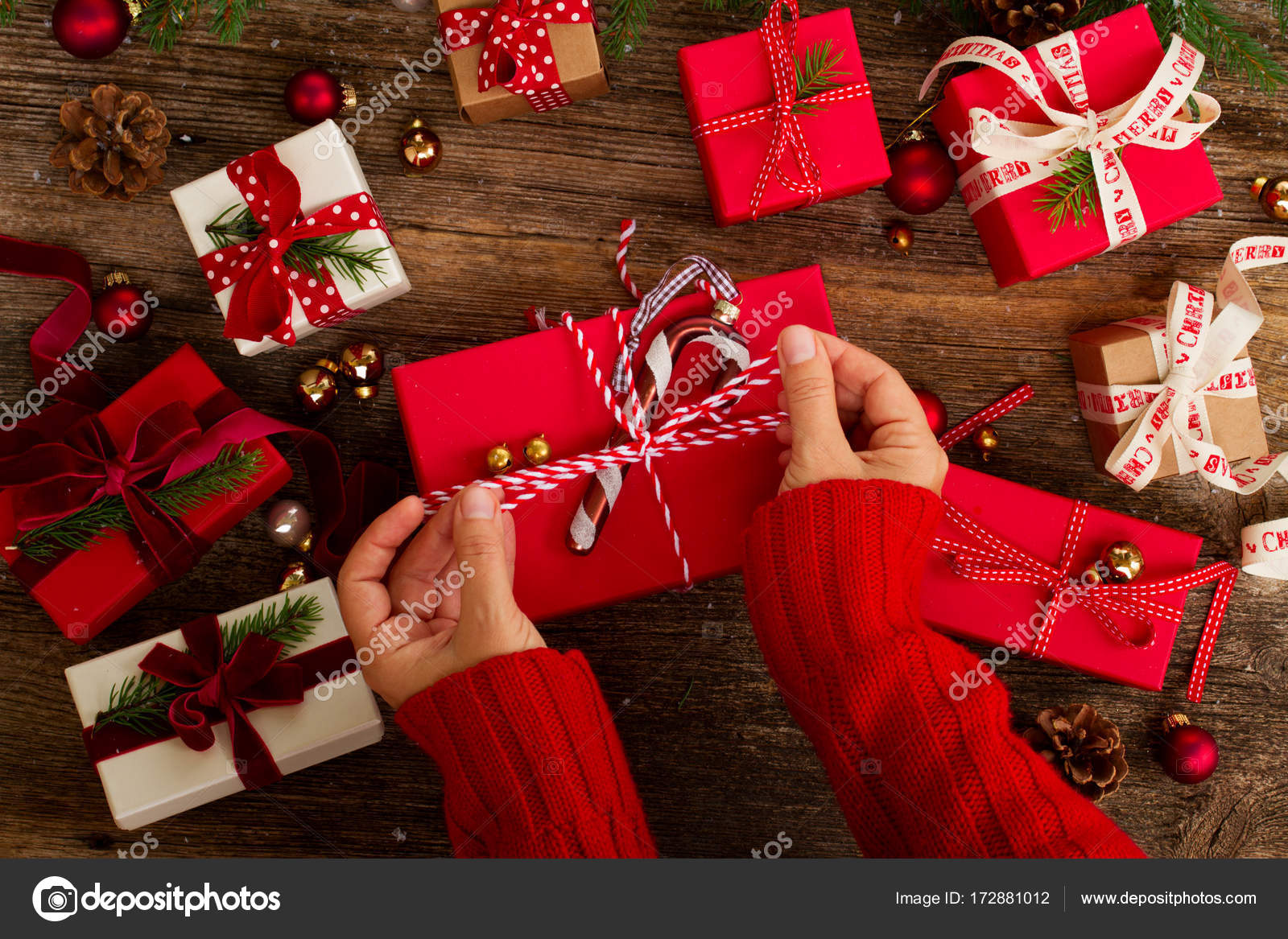Christmas gift giving stock photo neirfys 172881012 christmas gift giving hand wrapping red and white paper christmas gift boxes on wooden background photo by neirfys negle Images
