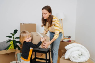 Son helping mother to pack, they are moving out from an old apartment.
