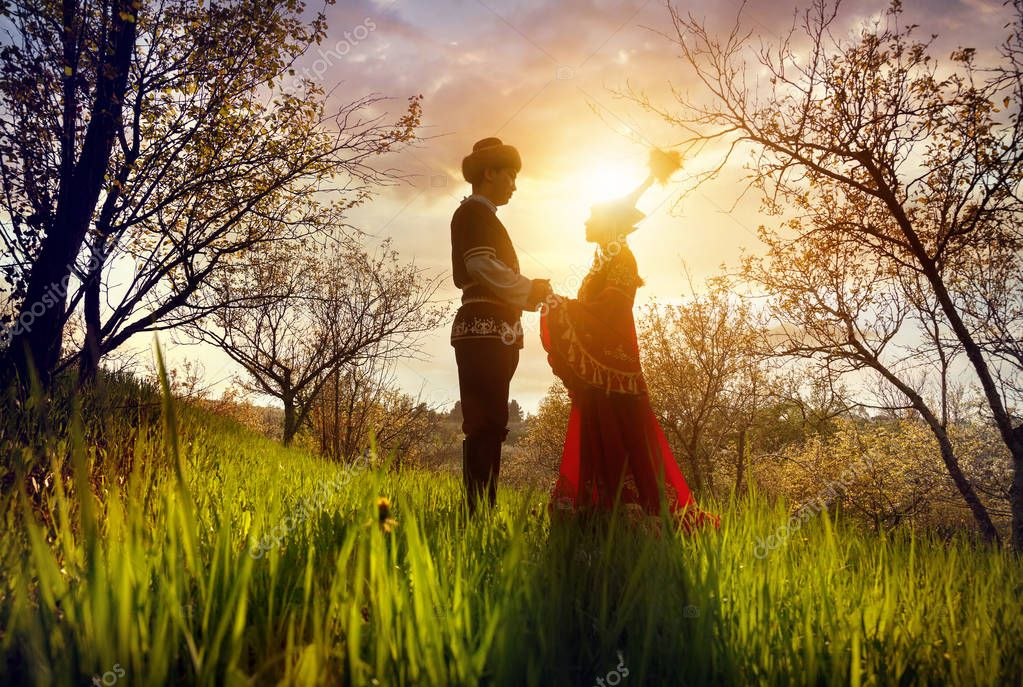 Kazakh couple in ethnic costume at sunset