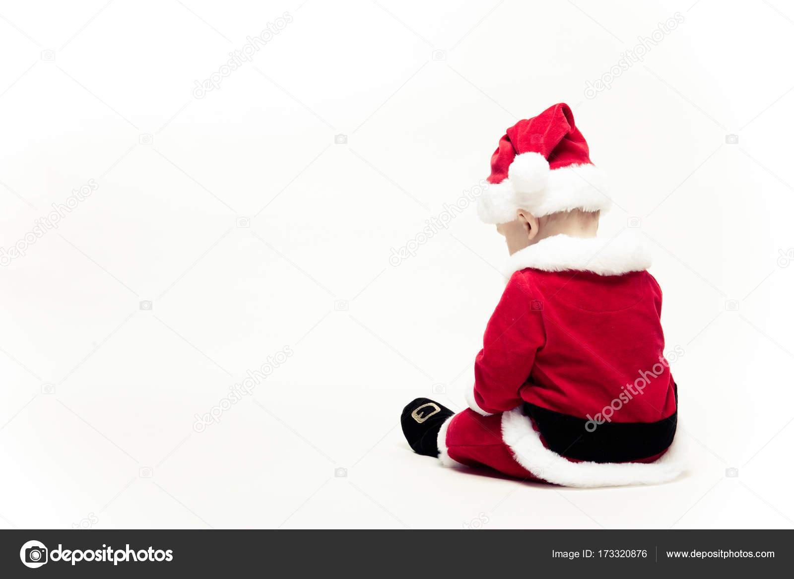 ed850c4bfd91c Bébé père Noël en habits de Noël rouges est assis avec son dos isolé sur  blanc– images de stock libres de droits