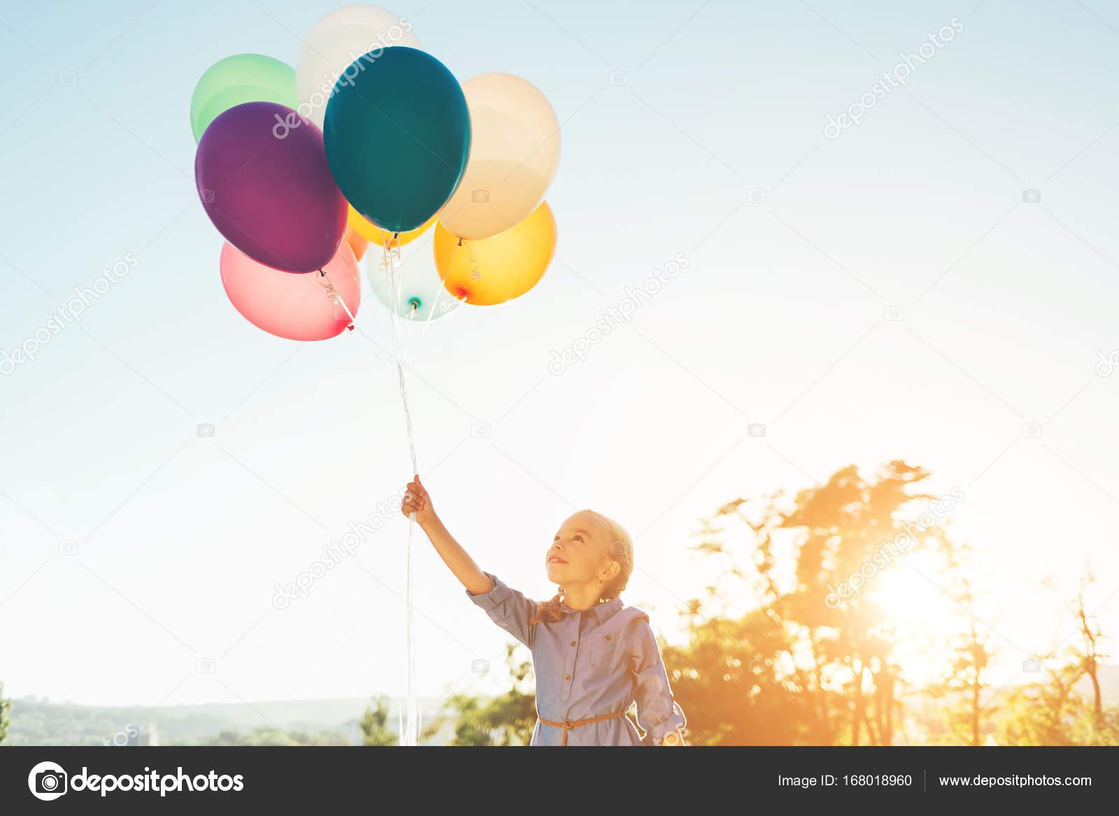 Дівчинка тримає повітряні кульки в одній руці 55b69553049fe