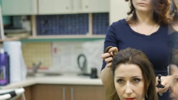 Pomocí žehličky na vlasy krásná žena v kadeřnictví kadeřník. Curling zvlnění