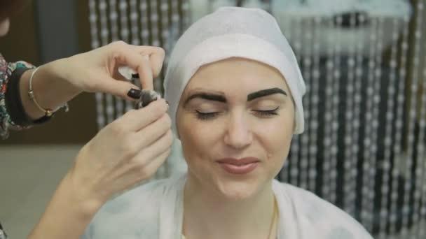 Closeup kosmetička rukou pomocí pinzety na Zenske obočí v salonu krásy