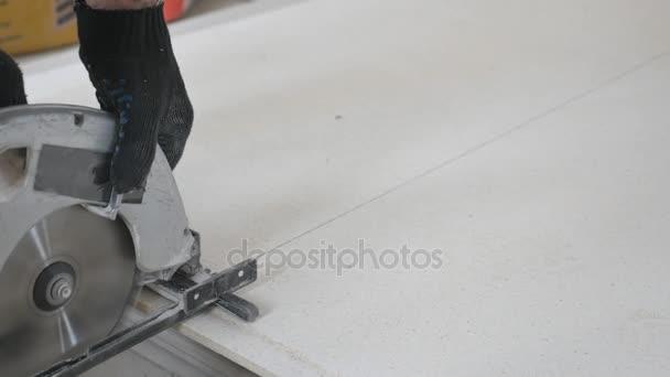 Dekorace na strop. Zaměstnance pila řeže sádrokartonové desky. Detail