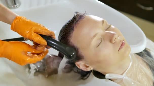Oplachování vlasů klienta v salonu krásy